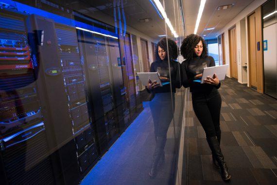woman using MacBook near server room
